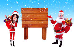Santa claus pointing towards a wooden sign Royalty Free Stock Photo