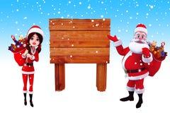 Santa claus pointing towards a wooden sign Royalty Free Stock Photo