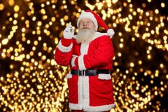 Santa Claus pointing up. Old Santa Claus in red costume and hat raised inex finger and looking upwards. Santa Claus and New Year fairytale Royalty Free Stock Photography