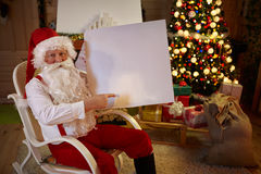 Santa Claus pointing at white banner Royalty Free Stock Photo