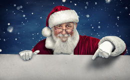 Santa Claus pointing in white blank sign with smile. On winter snow  background Royalty Free Stock Photos