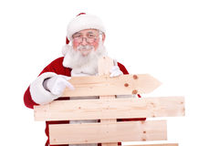 Santa Claus pointing wooden sing. Santa Claus pointing in blank wooden sing, isolated on white background stock image