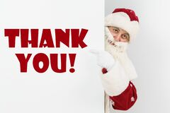 Santa Claus points his fingers at the board with the text - THANK YOU