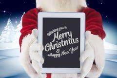 Santa Claus pokazuje cyfrową pastylkę z bożego narodzenia powitaniem Obrazy Royalty Free