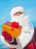 Santa Claus-Porträt mit goldenem Geschenk auf Seestrand Stockfotos