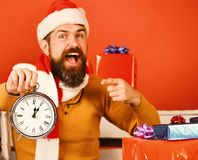 Santa Claus portrait pointing at clock showing five to midnight. Santa Claus portrait pointing at clock showing five minutes to midnight, studio on red royalty free stock images
