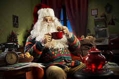 Santa Claus. Portrait of Santa Claus sitting on armchair holding a cup of tea Stock Photos
