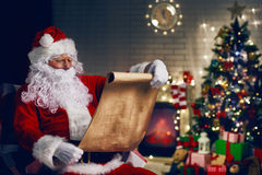 Santa Claus. Portrait of Santa Claus sitting at his room at home near Christmas tree Stock Image