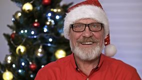 Santa Claus portrait, sitting indoor near decorated xmas tree with lights - Merry Christmas and Happy Holidays stock video footage