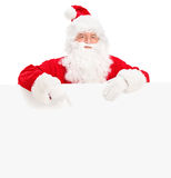 Santa claus posing behind a blank billboard and pointing. Isolated on white background, shot with a tilt and shift lens Stock Photo