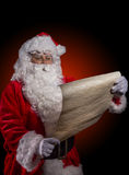 Santa Claus posing on dark red background. Santa Claus with wish list posing on dark red background Royalty Free Stock Photography