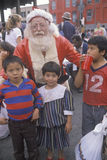 Santa Claus posing with homeless children at Christmas dinner, Los Angeles, California Stock Photo