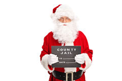 Santa Claus posing for a mug shot. Studio shot of a criminal Santa Claus posing for a mug shot with a black board in his hand isolated on white background Stock Images