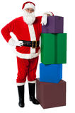 Santa Claus posing beside pile of gifts Stock Image