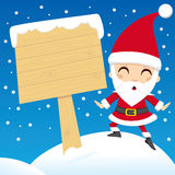 Santa Claus Post. Santa Claus standing next to a blank wooden sign post Royalty Free Stock Image