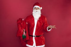 Santa Claus is powerless for lack of gifts. On the red background Royalty Free Stock Images