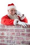 Santa Claus pozycja obok kominu i opowiadać na telefonie komórkowym Zdjęcie Royalty Free