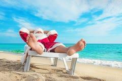 Santa Claus prendente il sole che si rilassa nel bedstone sulla spiaggia - Natale Fotografie Stock