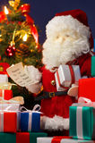 Santa Claus preparing Christmas presents. (vertica Stock Photo