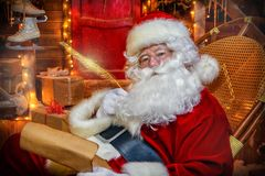 Thoughtful santa claus. Santa Claus is preparing for Christmas. He writes letters. House of Santa Claus. Christmas decoration stock photos