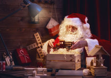 Santa Claus is preparing gifts. Merry Christmas and Happy Holidays! Santa Claus is preparing gifts for children for Xmas at his desk at home. Christmas legends Royalty Free Stock Photos