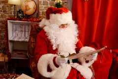 Santa Claus preparing for travel and looking at the world map stock images