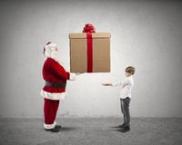 Santa Claus with present for a child Stock Images