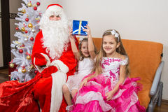 Santa Claus presented first gift girls Stock Image