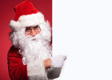 Santa claus is presenting a blank board by pointing Stock Images