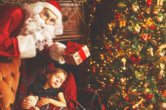 Santa Claus presents Christmas gift to sleeping child girl in Ch Royalty Free Stock Images