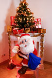 Santa Claus with presents in front of Christmas tree and chimney stock images