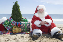 Santa Claus With Presents And Tree, die auf Strand sitzt Lizenzfreie Stockfotografie