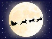 Santa Claus pulka över moonen Arkivbild