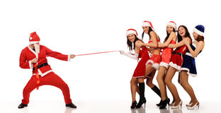 Santa Claus pull five women. Santa Claus pull five beauty girls in Christmas costumes, isolated on white. may be use for fashion Christmas cards and posters stock photo
