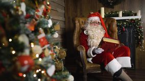 Santa Claus pulling out old red silk album near christmas tree with toys and lights stock video