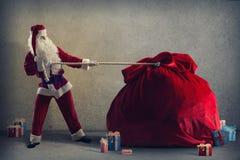 Santa Claus pulls a huge bag of gifts Royalty Free Stock Photos