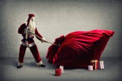 Santa Claus pulls a huge bag of gifts Stock Photos