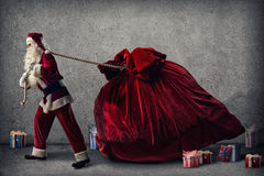 Santa Claus pulls a huge bag of gifts Stock Photography