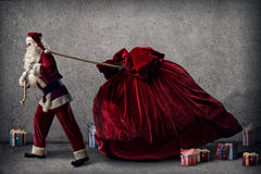 Santa Claus pulls a huge bag of gifts Stock Images