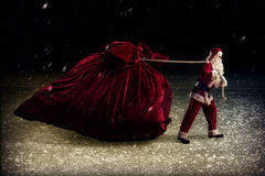 Santa Claus pulls a huge bag of gifts Royalty Free Stock Photography