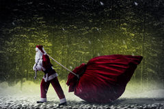 Santa Claus pulls a huge bag of gifts. Santa Claus in a night winter forest pulling a huge bag of gifts Stock Images