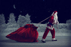 Santa Claus pulls a huge bag of gifts. Santa Claus in a night winter forest pulling a huge bag of gifts Royalty Free Stock Images