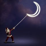 Santa Claus pulls the moon Stock Image