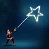 Santa Claus pulls the shining star Stock Photo