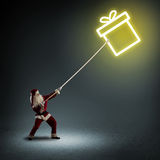 Santa Claus pulls a symbol box with a gift Stock Photos