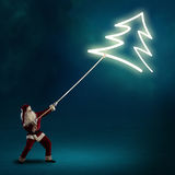 Santa Claus pulls a symbol of the Christmas tree Stock Photos