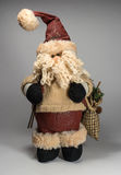 Santa Claus-Puppe, die eine Strickjacke trägt In den Händen von Skipfosten und -tasche mit Geschenken Stockfoto