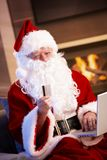 Santa Claus purchasing on internet. Santa Claus using computer purchasing on internet paying with credit card Royalty Free Stock Image