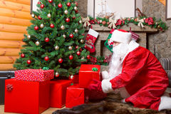 Santa Claus puts gift boxes under christmas tree. Bearded Santa Claus puts gift boxes under christmas tree, fireplace on background Royalty Free Stock Photos