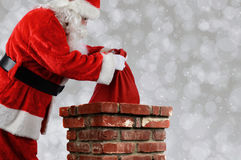 Santa Claus Putting Bag into Chimney. Closeup of Santa Claus placing his bag inside a chimney. Horizontal with copy space over a light bokeh background Royalty Free Stock Photos